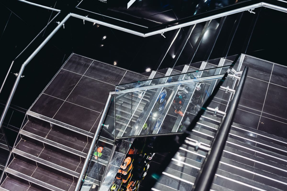 mezzanine floor staircase with black tiles, chrome handrails and glass balustrades. At JD sports flagship retail store in Birmingham UK